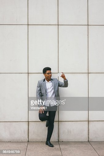 Young man leaning against a wall taking a selfie