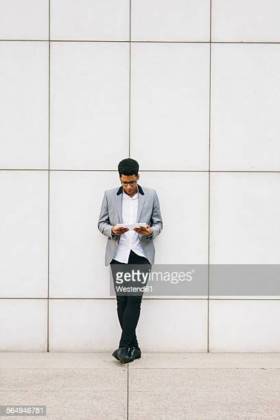 Young man leaning against a wall using a digital tablet