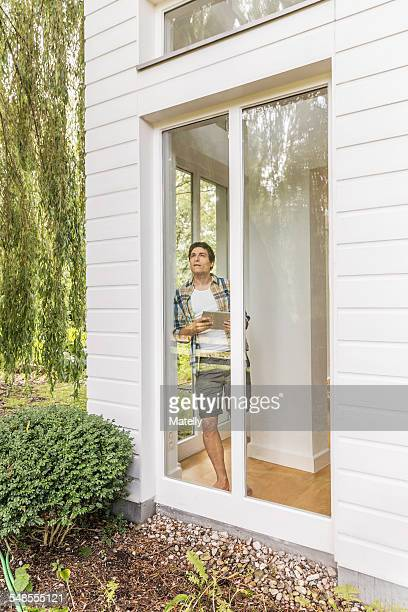 Young man leaning against and looking out of house window