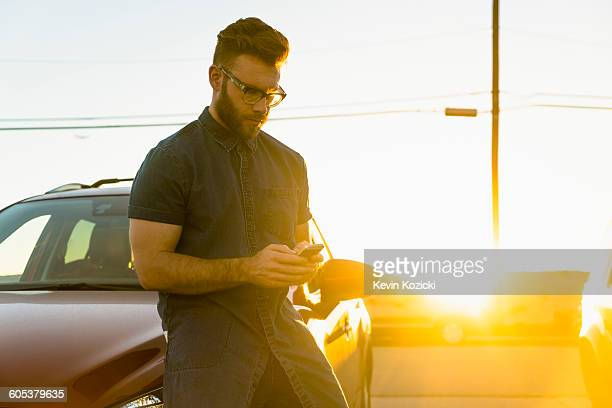 Young man leaning against car, using smartphone