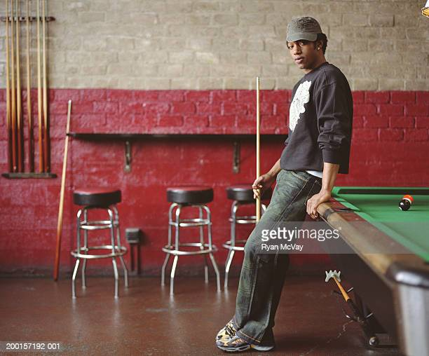 Young man leaning against pool table, holding pool cue, portrait