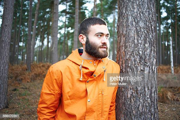 Young man leaning against tree looking out from forest