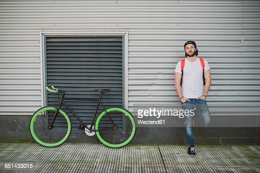 Young man leaning against wall next to fixie bike