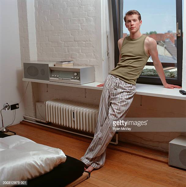Young man leaning against window sill, indoors, portrait
