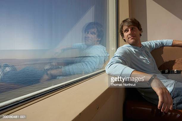 Young man leaning against window sill on ferry, side view