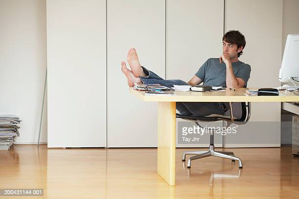 Young man leaning back in chair, feet on desk, resting head on hand