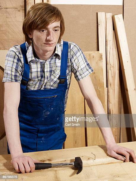 A young man leaning on a bench in a wood workshop