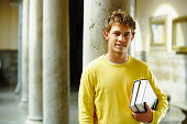 Young man leaning on column holding books, smiling, portrait