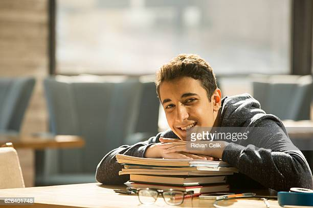 Young man leans on stack of books