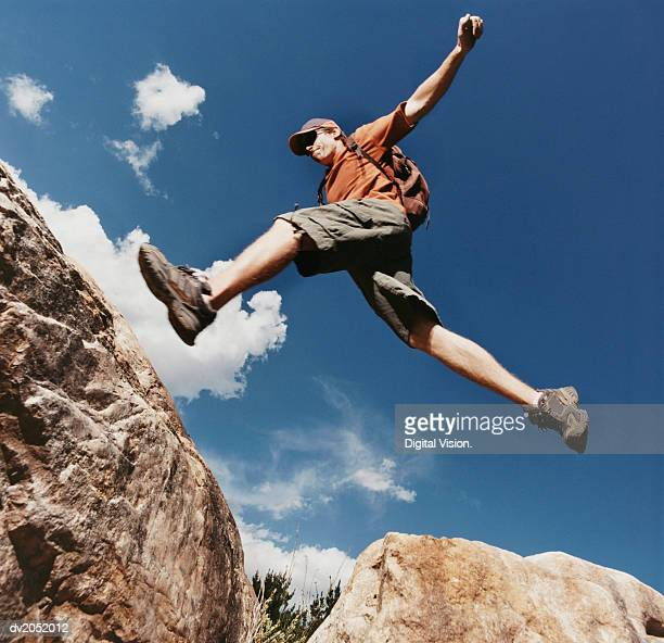 Young Man Leaping Between Rocks
