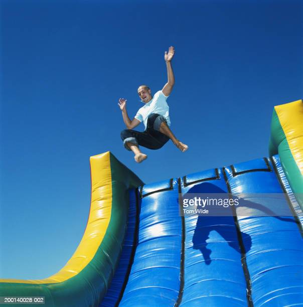 Young man leaping down inflatable slide outdoors, low angle view