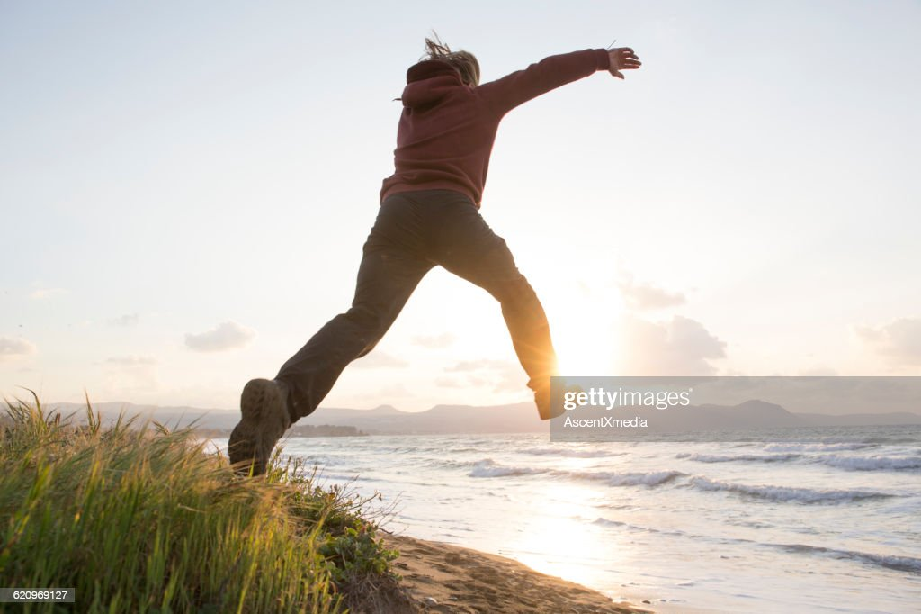 Young man leaps from beach dune, towards sea, sun