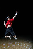 Young man leaps high in the air and prepares to smash a shuttlecock during a game of badminton.