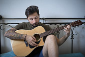 Young Man Learn Play Acoustic Guitar in his Bed