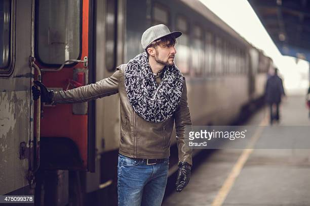 Young man leaving the train at railroad station.