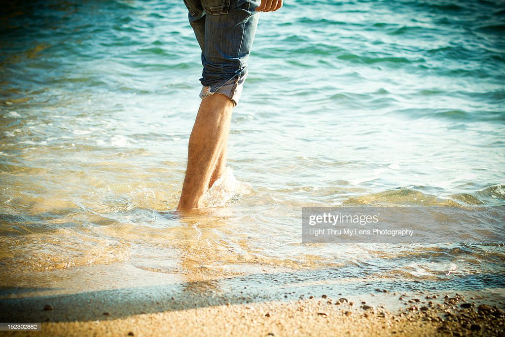 Young man legs walking into the sea : Stock Photo