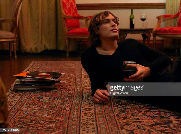 Young Man Lies on a Rug Next to a Pile of Records, Holding a Glass of Red Wine and Looking up in Contemplation