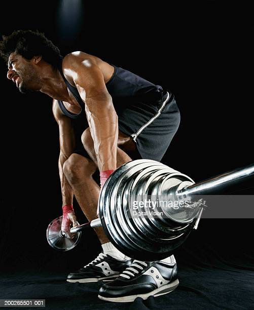 Young man lifting barbell, low angle view