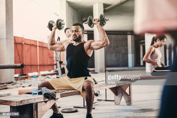 Young man lifting dumbbell in a Urban  Gym