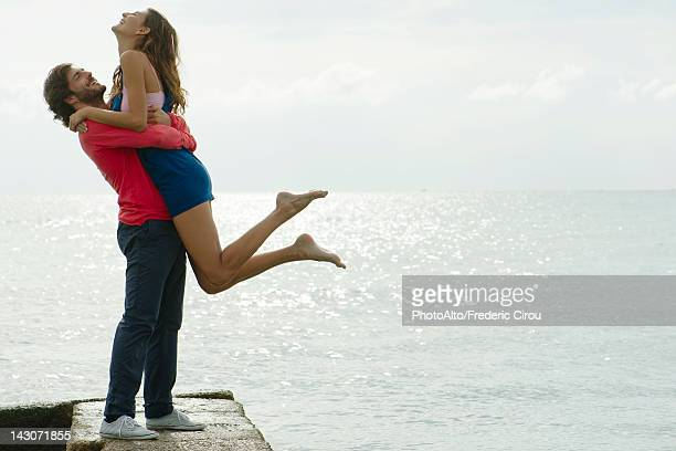 Young man lifting girlfriend up, portrait