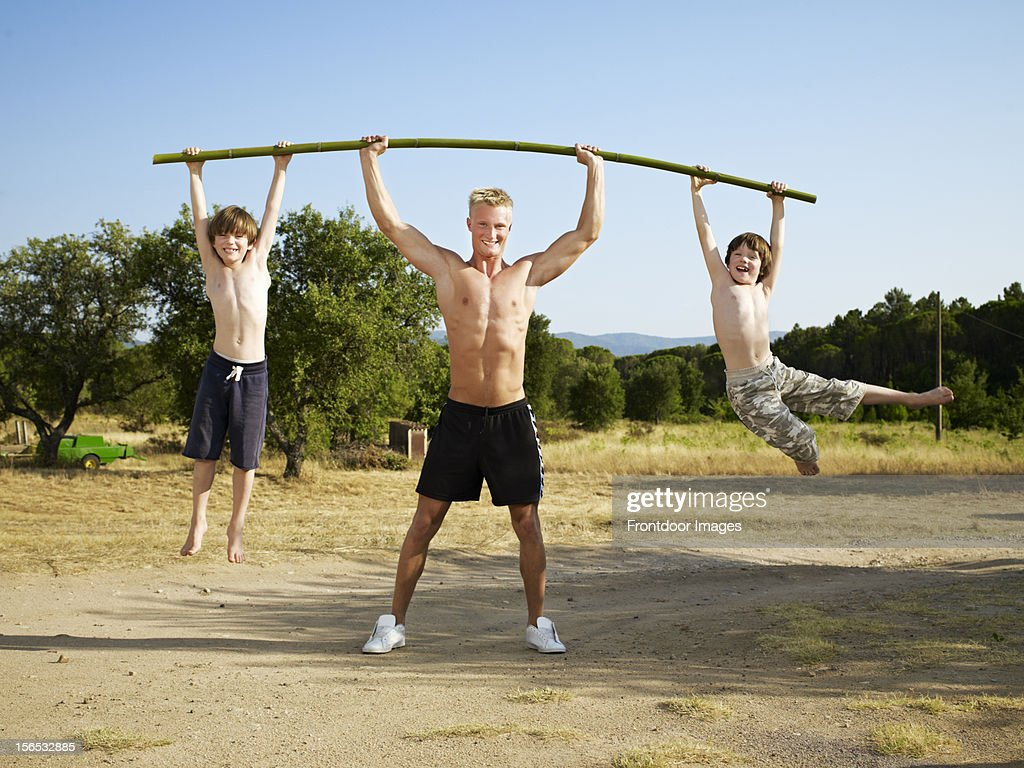 Young man lifting two young boys with a bamboo bar : Stock Photo