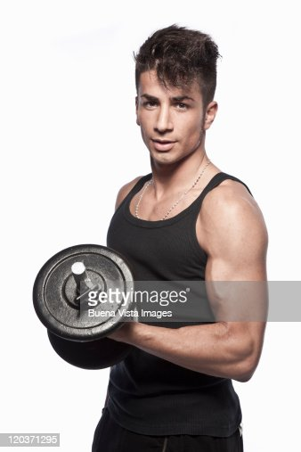 Young man lifting weights : Stock Photo