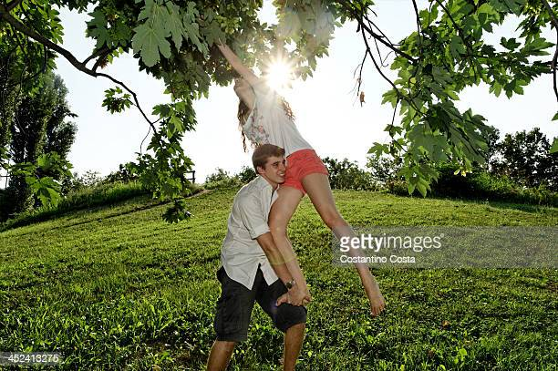Young man lifting young woman to tree branches