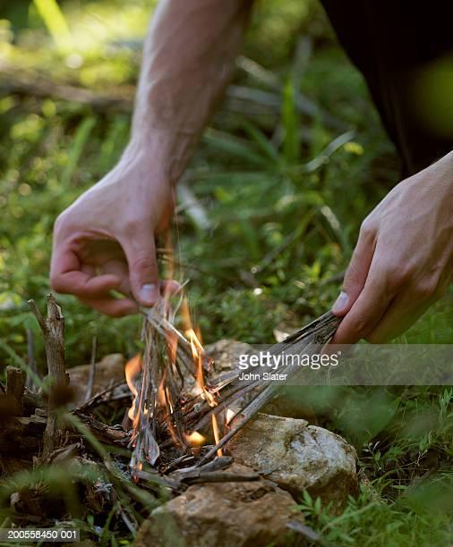 Young man lighting kindling outdoors