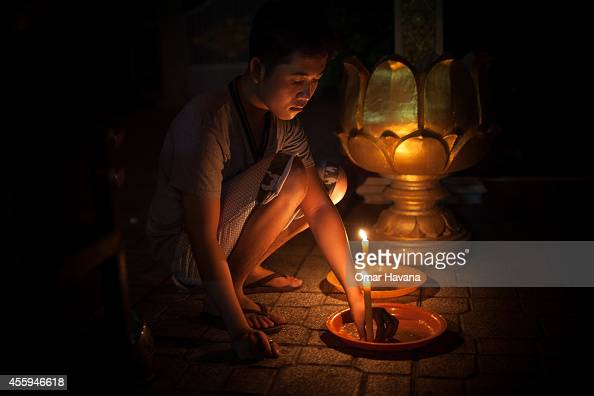 A young man lights a candle in Wat Lang Ka pagoda during Pchum Ben festival on September 23 2014 in Phnom Penh Cambodia Pchum Ben or 'Feast Festival...