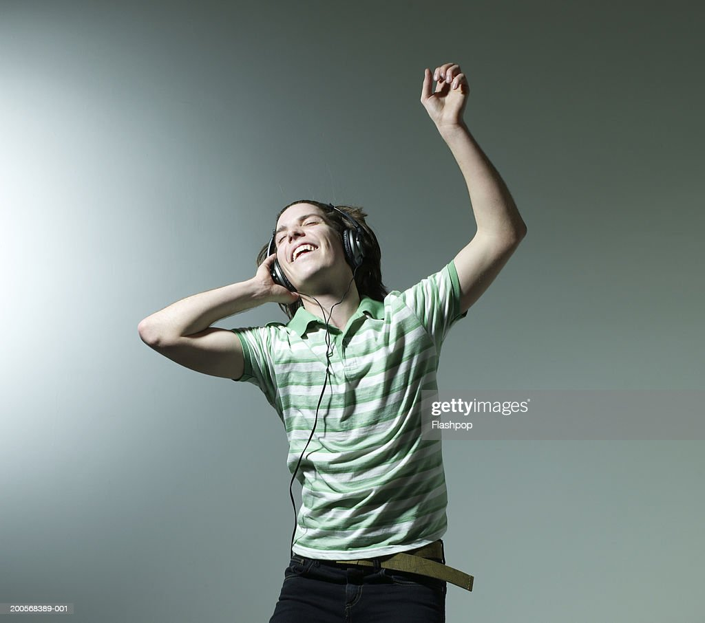 Young man listening headphones and dancing : Stock Photo