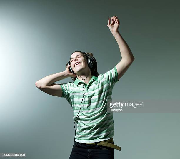 Young man listening headphones and dancing