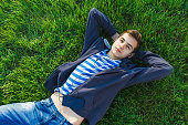 Teenage man in park in spring, listening music with headphones, smart phone on grass. Rest and dream.