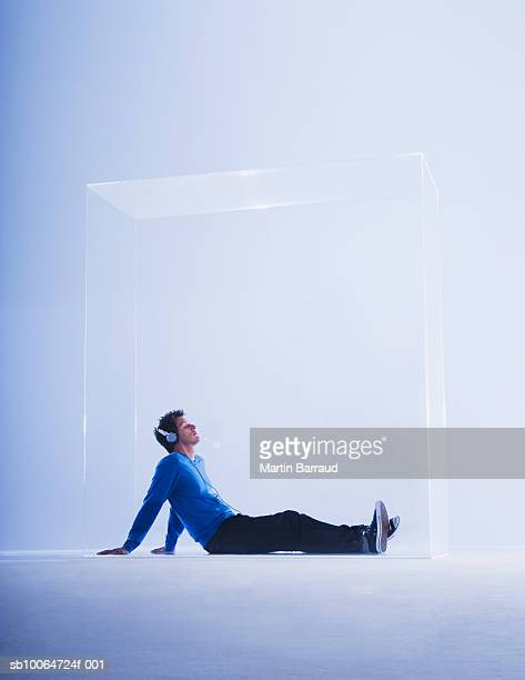 Young man listening music in glass cabinet