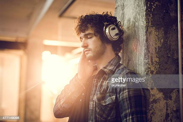 Young man listening music on headphones with his eyes closed.