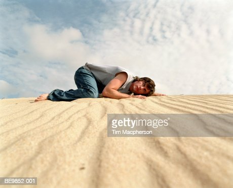 Young man listening to ground on sand dune