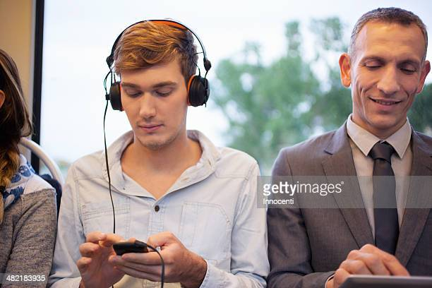 Young man listening to headphones and using smartphone on train