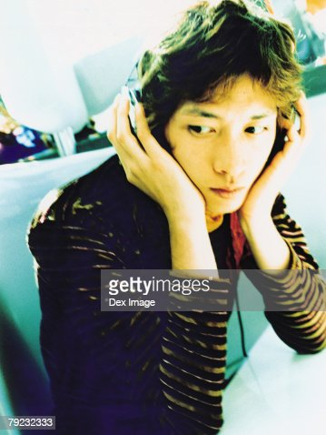 Young man listening to headphones, portrait, close up : Stock Photo