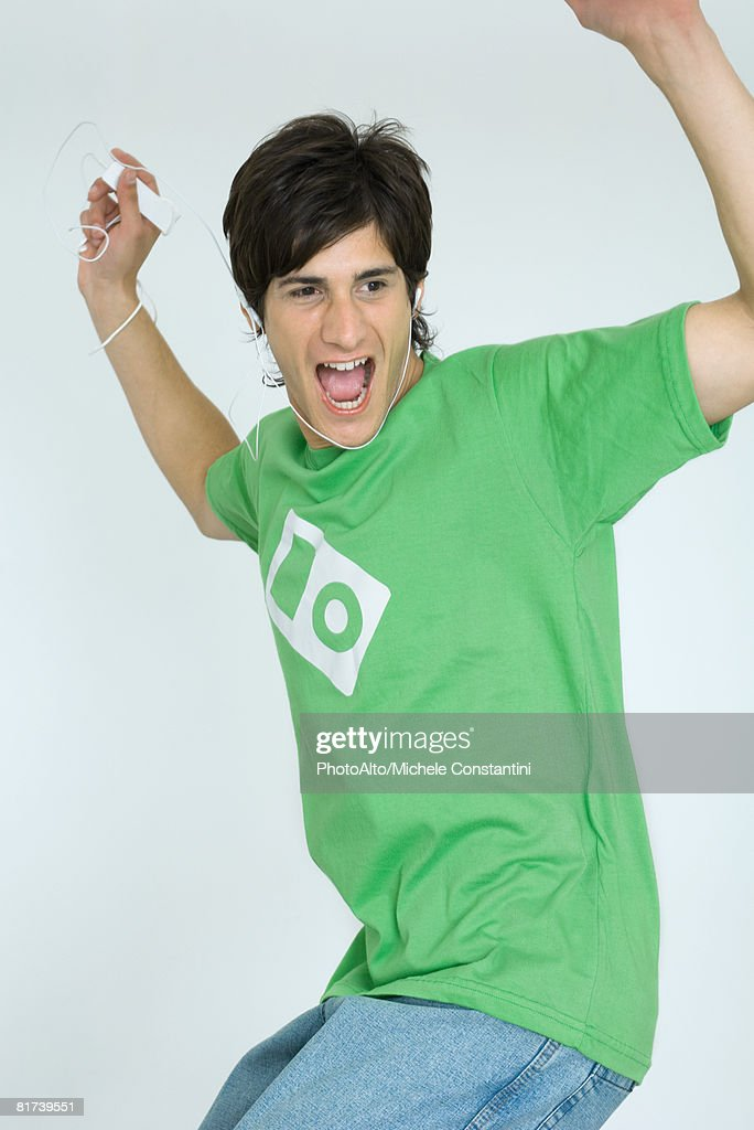 Young man listening to MP3 player, dancing, arms raised