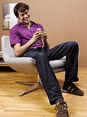Young man listening to MP3 player on armchair