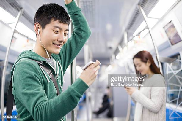 Young man listening to music in subway