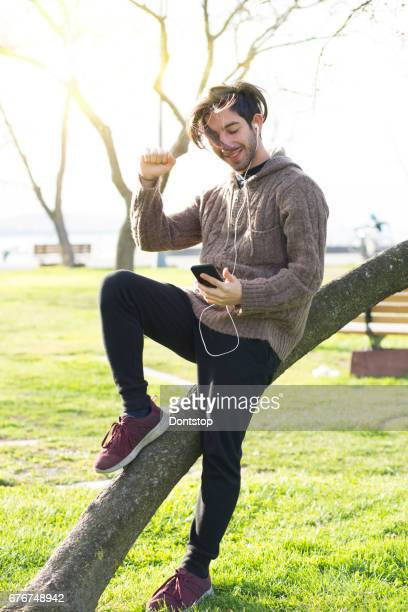 Young man listenning music on the tree in public park
