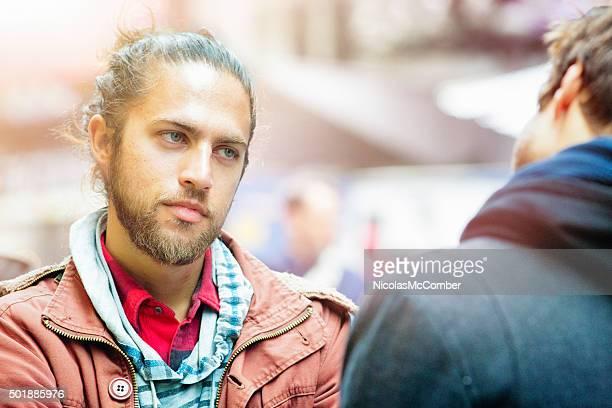 Junger Mann hört Freund mit schweren Ausdruck