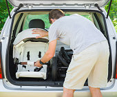 Young man loading parts of baby carriage in opened car trunk. Preparing to become parent for future child. Things transportation. Green outdoor nature and sunny summer day atmosphere.