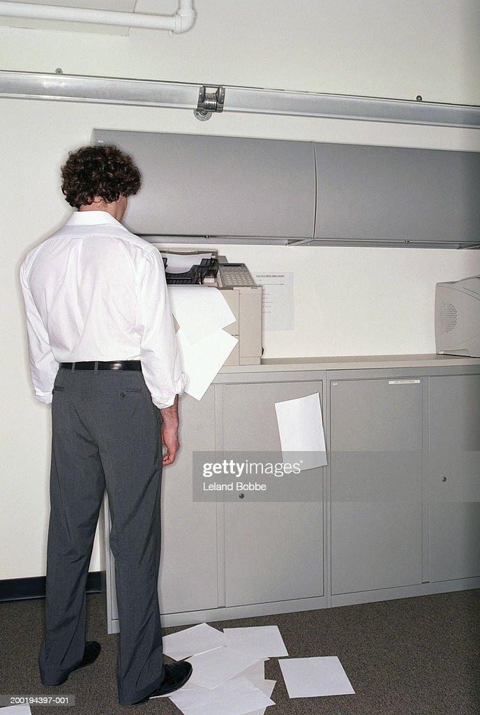 Young man look at malfunctioning printer, rear view