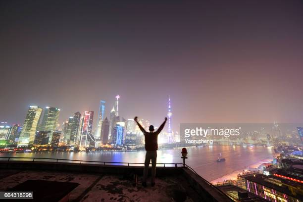 Young man lookin the night  of Shanghai city in the night,background building is  Lujiazui business center