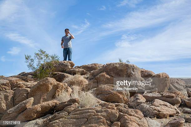 Young man looking around from hill in Anza-Borrego national park