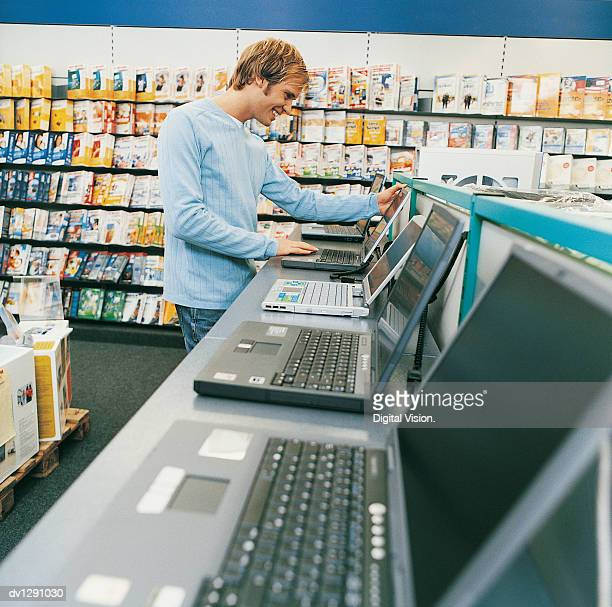 Young Man Looking at a Laptop in a Computer Shop