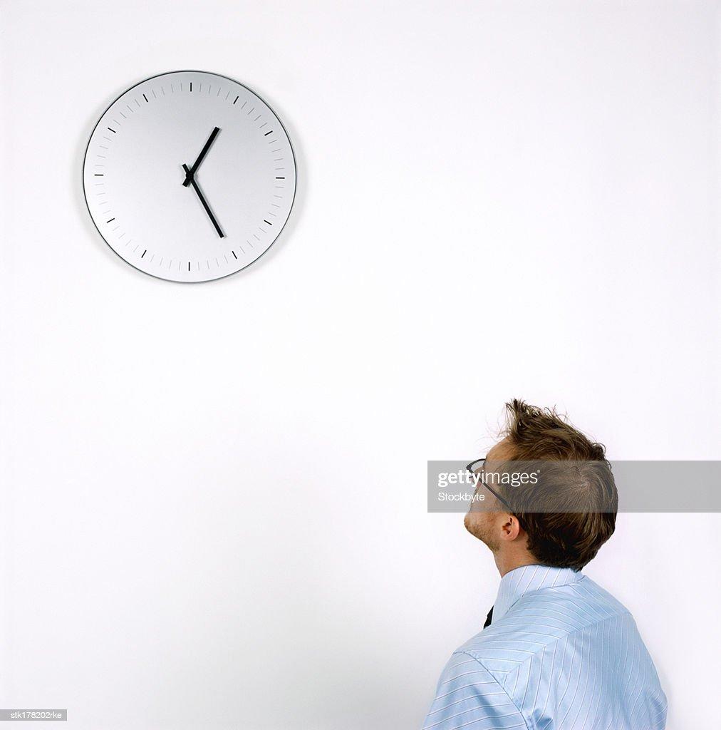 young man looking at a wall clock