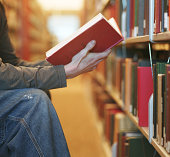 Young man looking at book in library, close-up of book