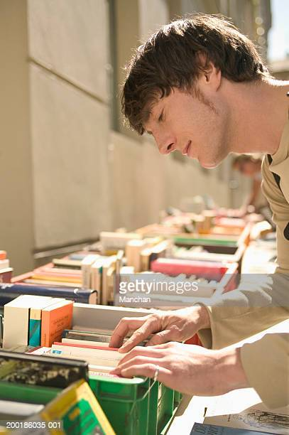 Young man looking at books in crate, side view
